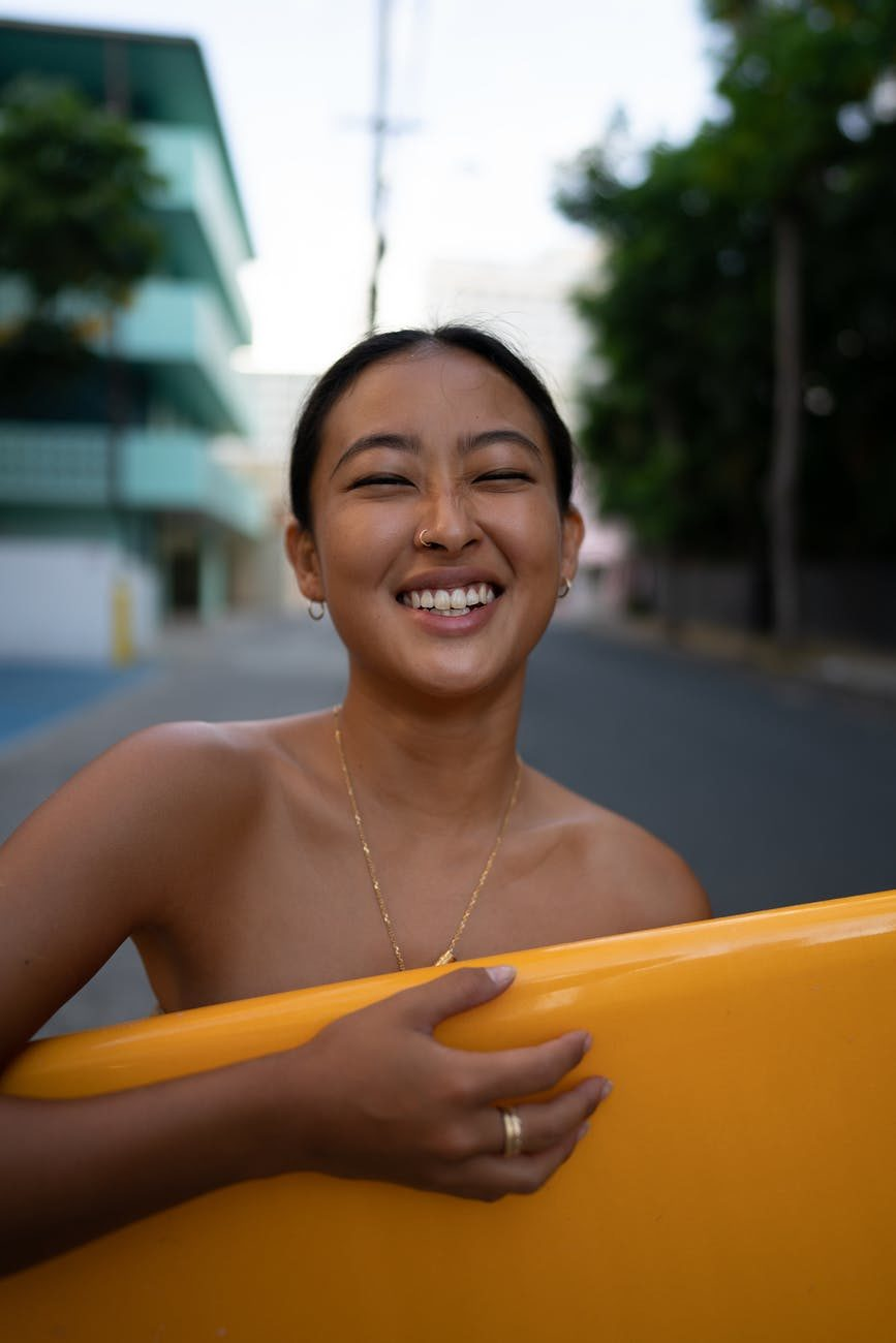 smiling ethnic lady standing with surfboard in town