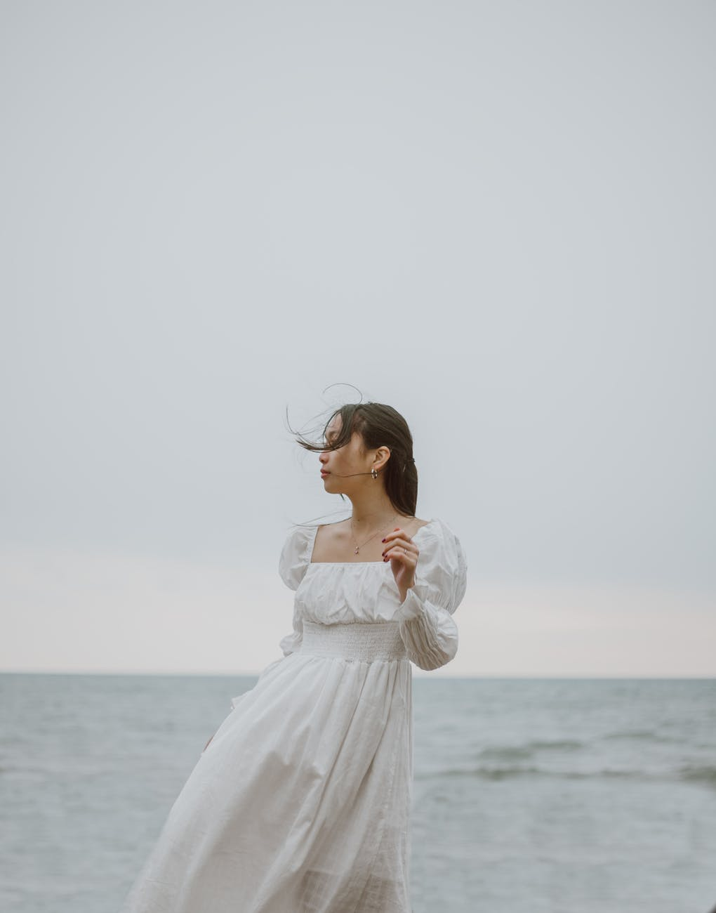 romantic asian traveler contemplating sea under light sky