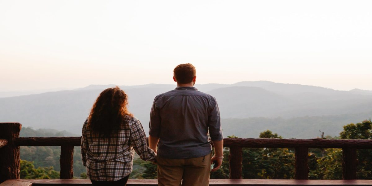 unrecognizable couple enjoying sunset over mountains during romantic trip