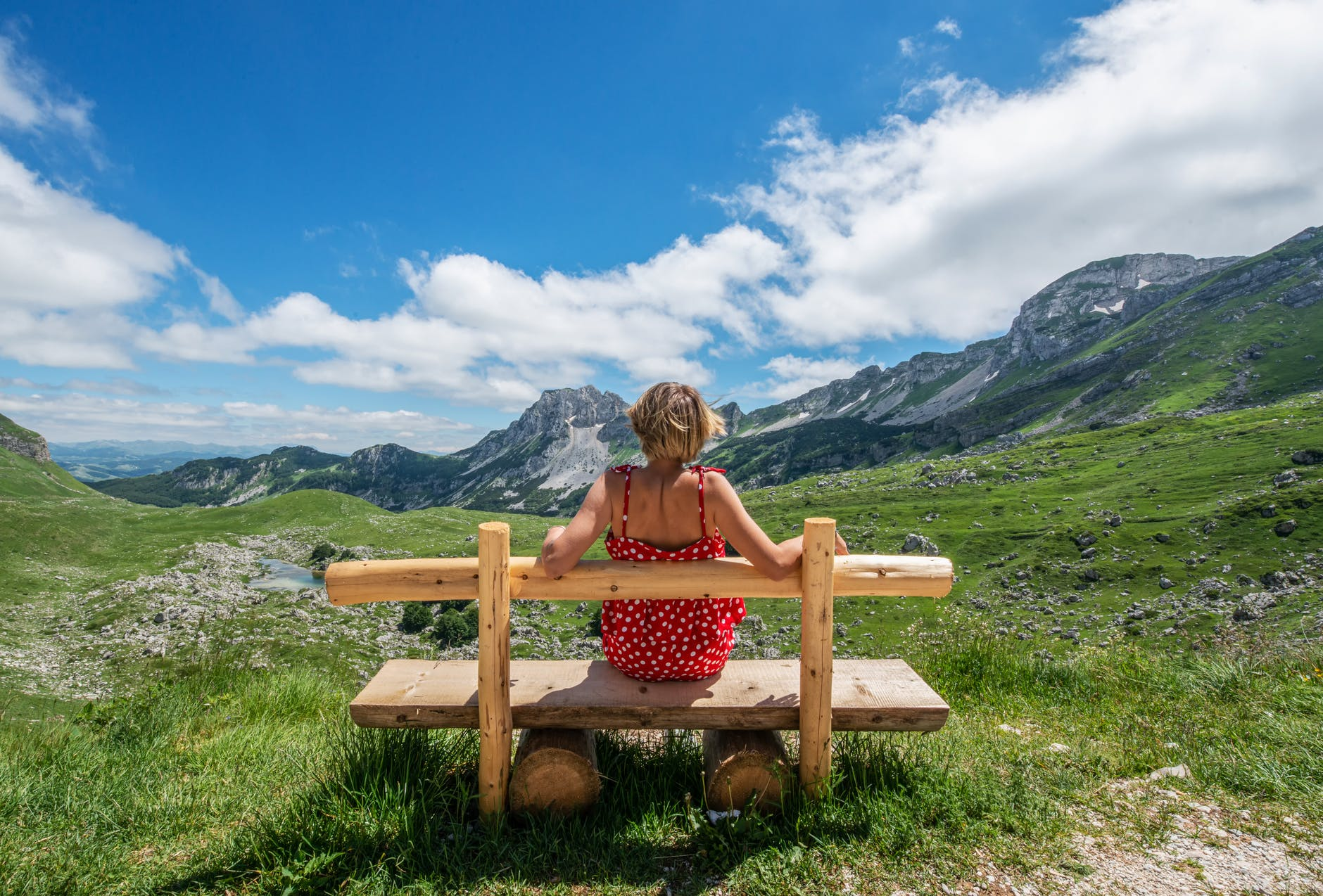 woman resting on wooden bench in meadow with fresh grass