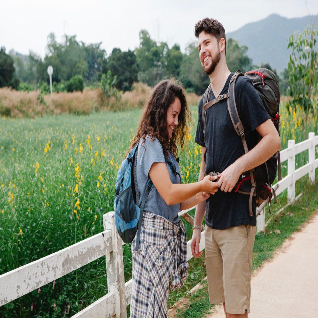 happy woman fastening backpack strap of boyfriend near meadow
