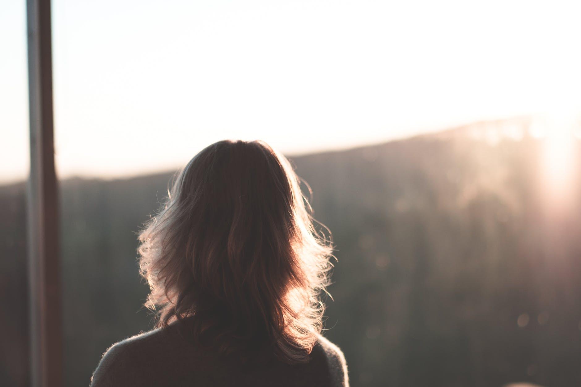 anonymous woman enjoying mountain view at sunset