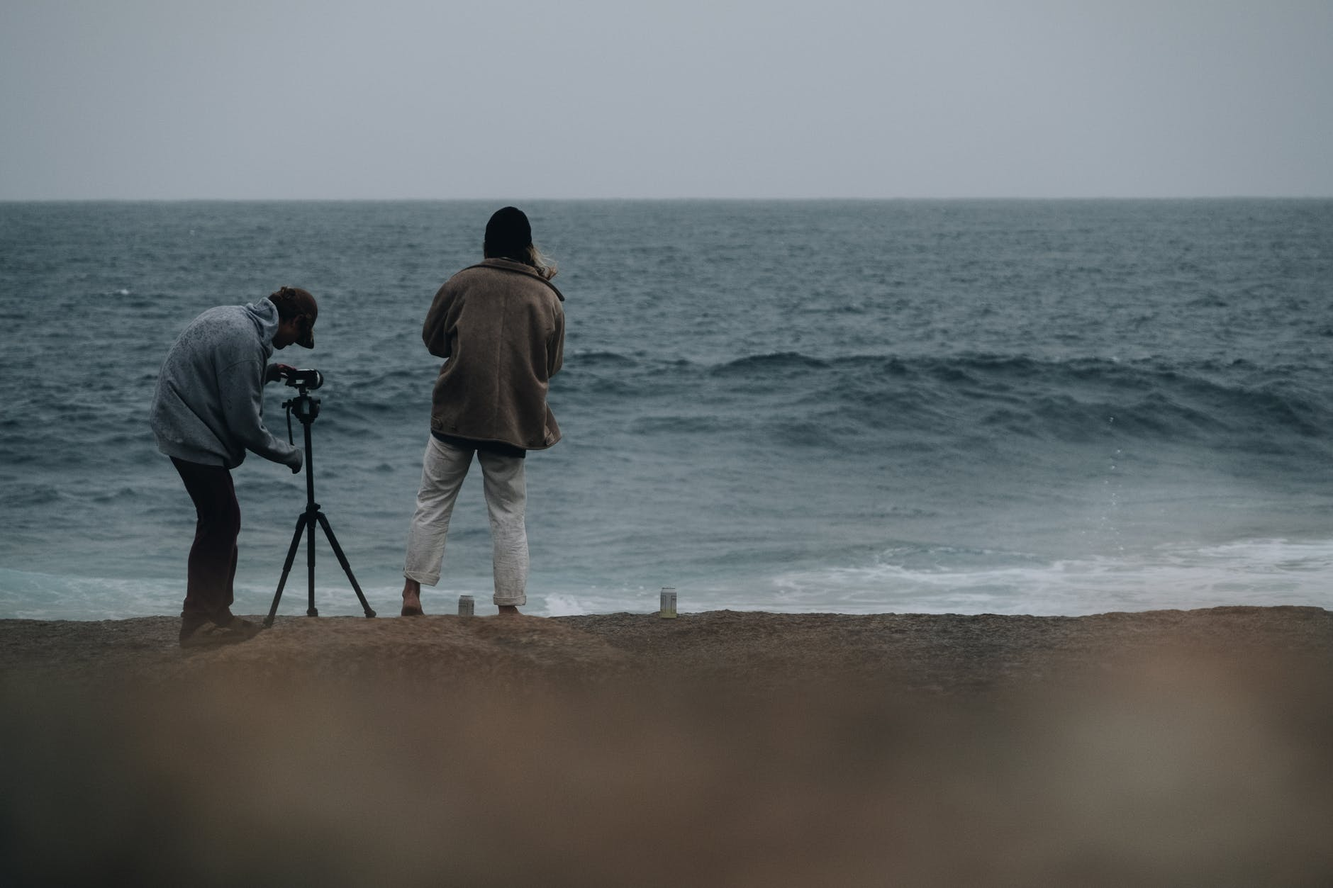 photographers shooting wavy ocean in cloudy day in daylight