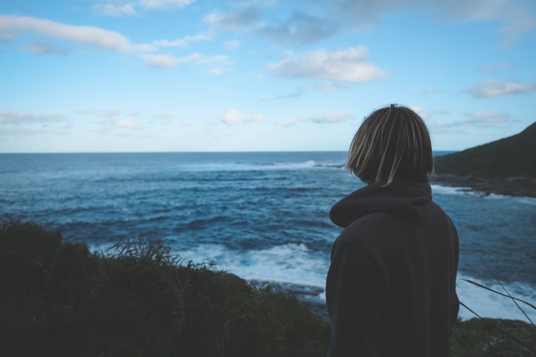 anonymous woman admiring wavy blue sea during trip at sundown