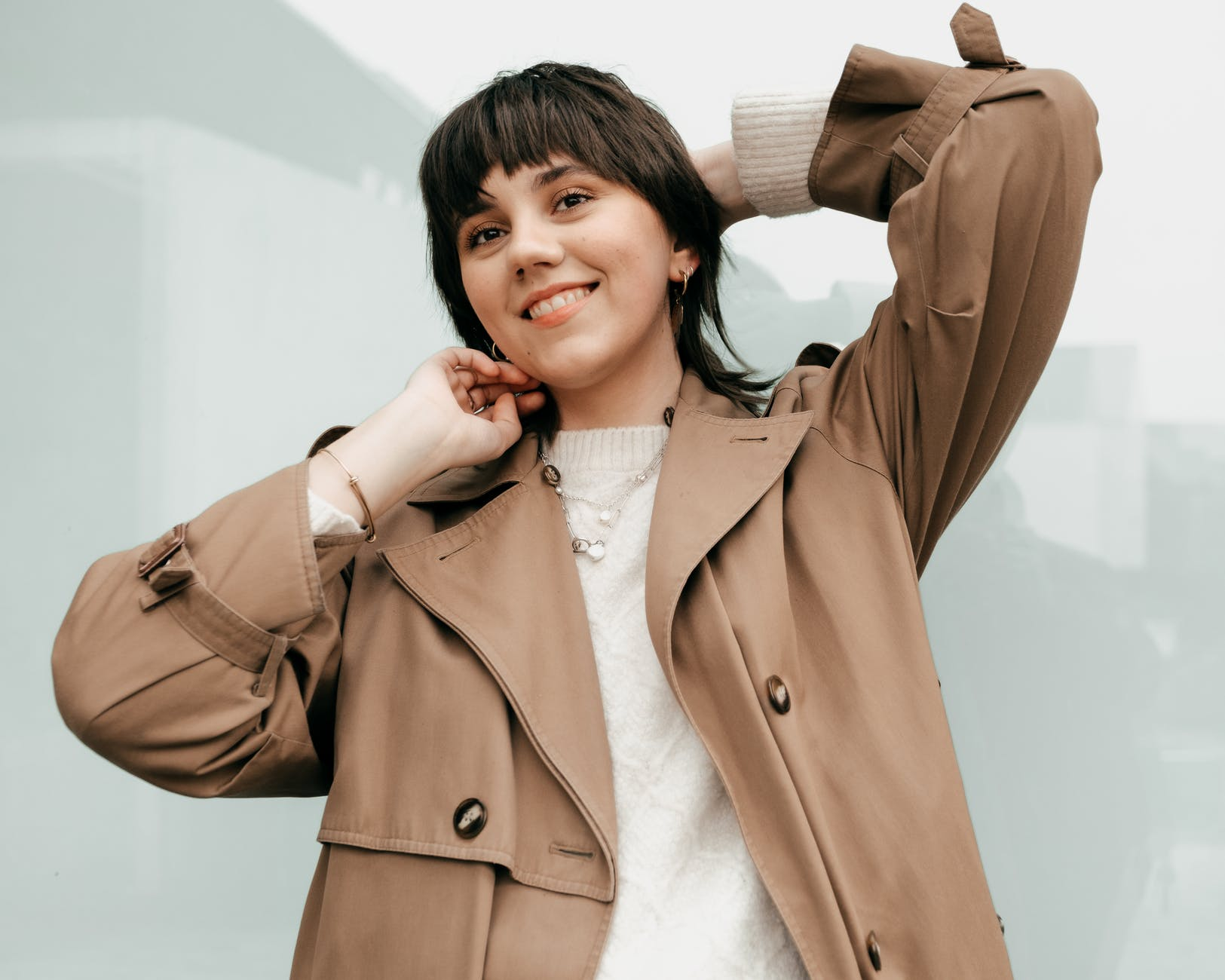 smiling female in trendy coat standing with raised hands