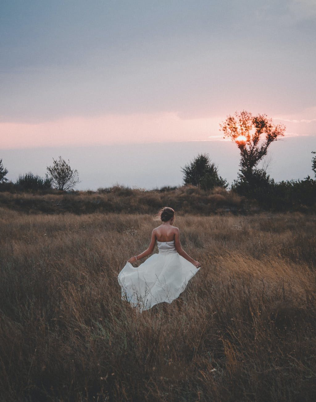 serene young woman in white dress walking in rural meadow at sundown