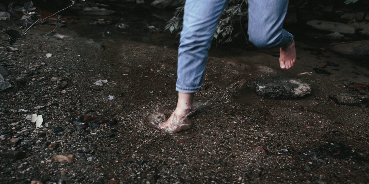 person in blue denim jeans standing on brown soil