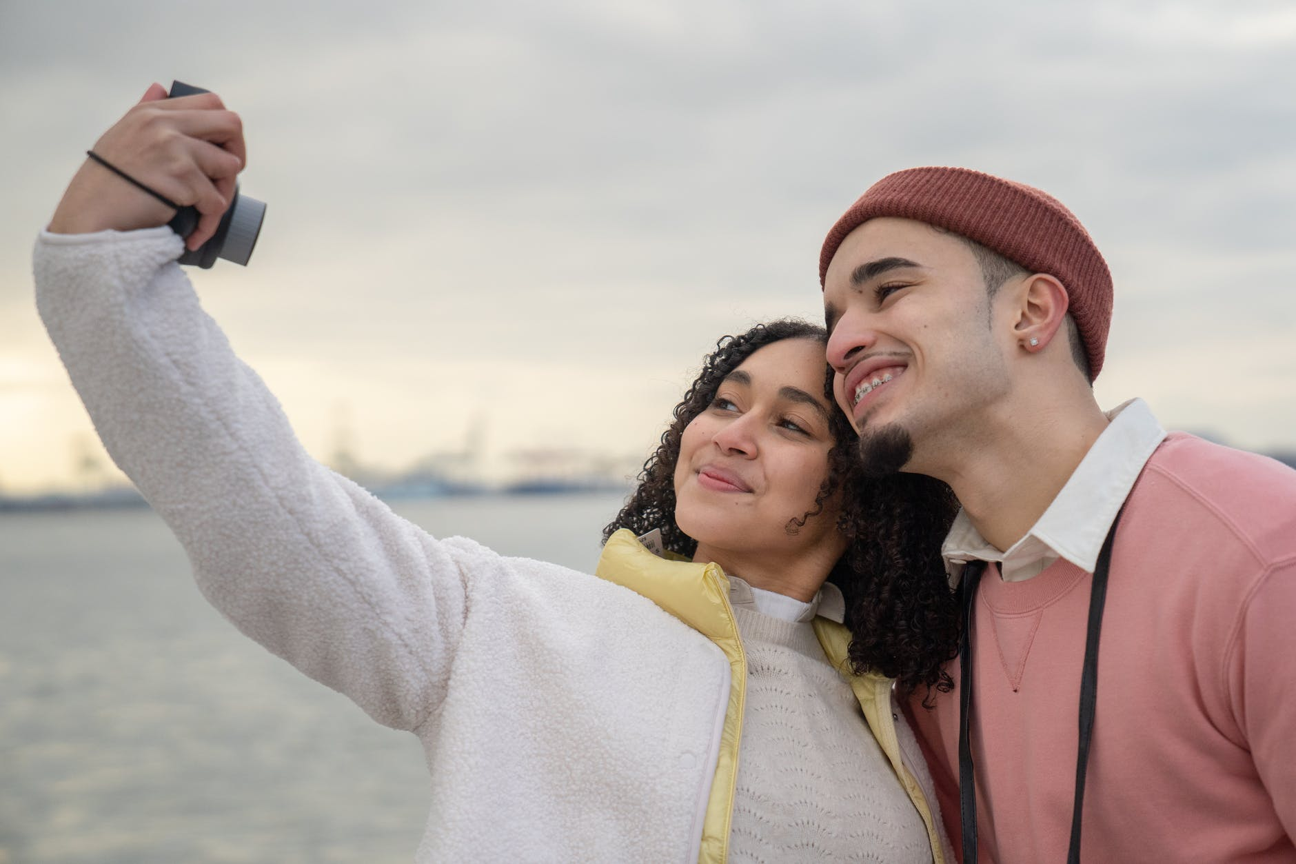 hispanic couple taking self photo on film camera near river