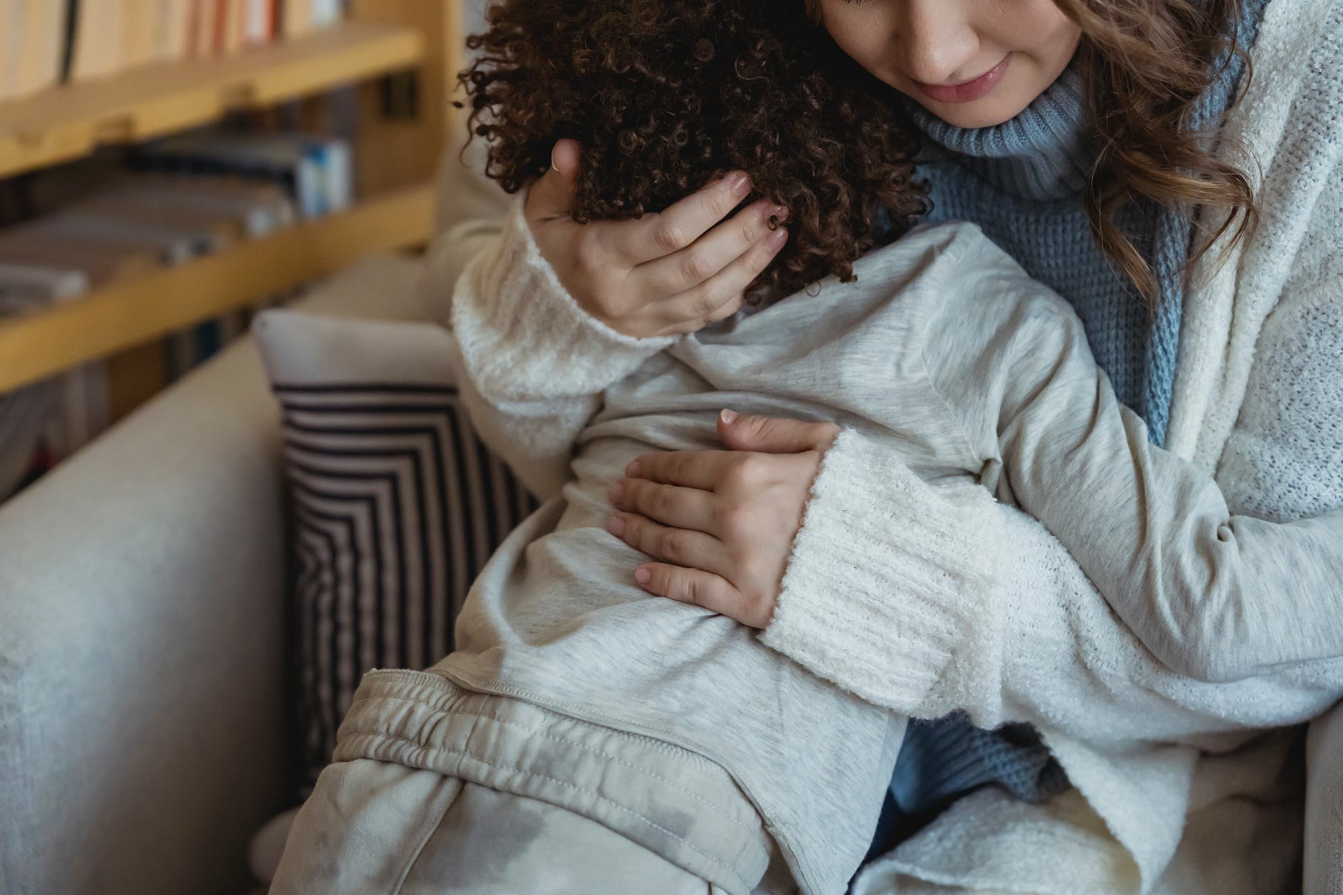 crop mother hugging toddler in light room
