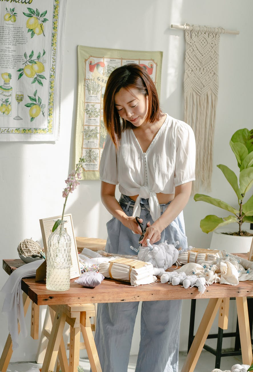 young asian craftswoman cutting tied clothes in modern shibori workshop