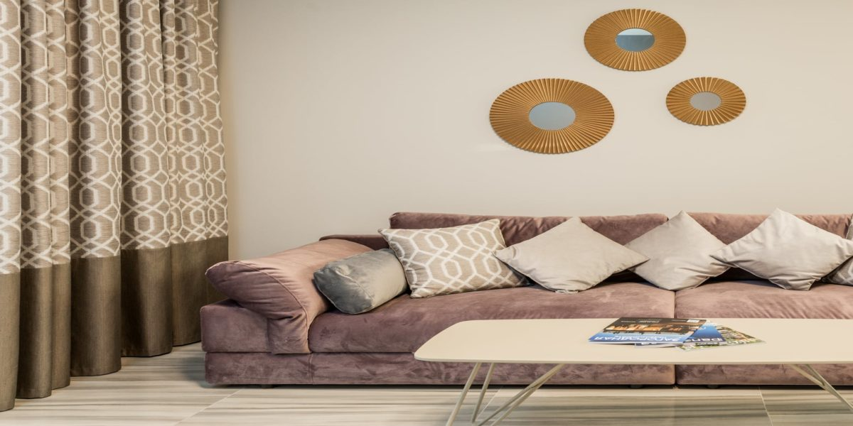 soft couch with pillows at wall decorated with mirrors