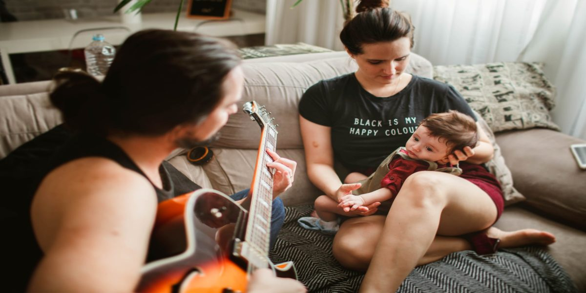 father playing guitar for mother with baby