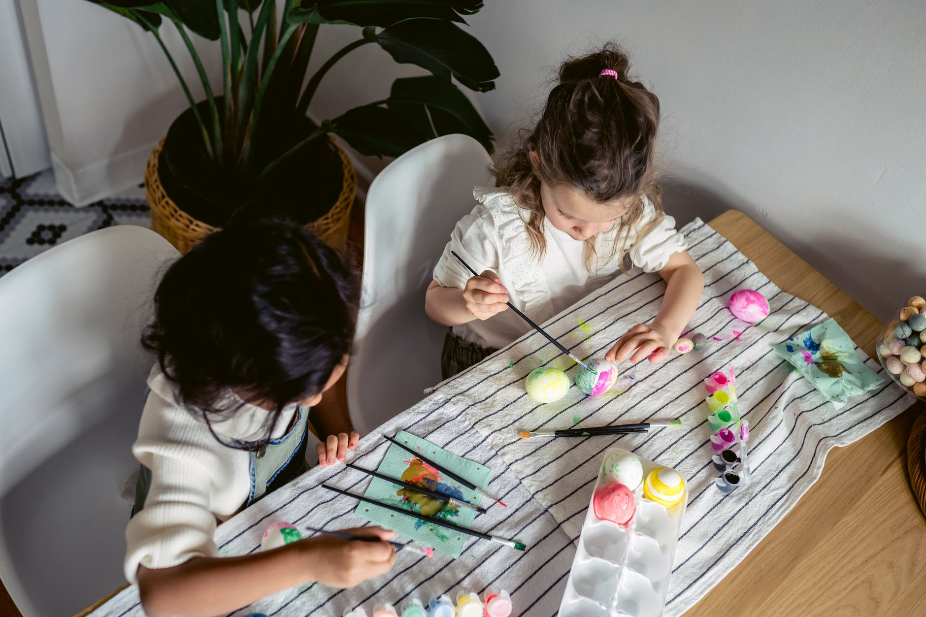 girls painting eggs on the table