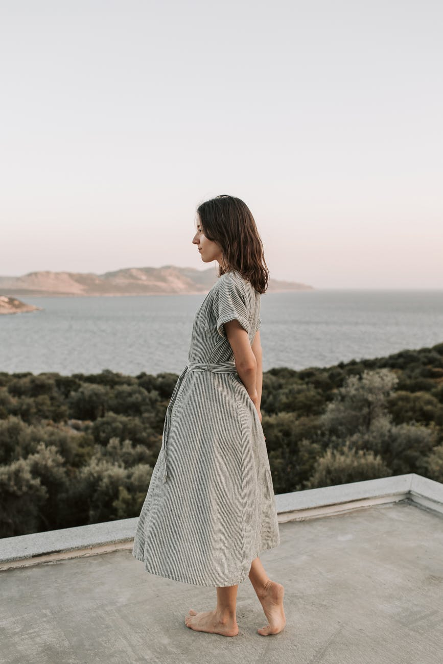 woman in gray dress standing on gray concrete looking at the sea