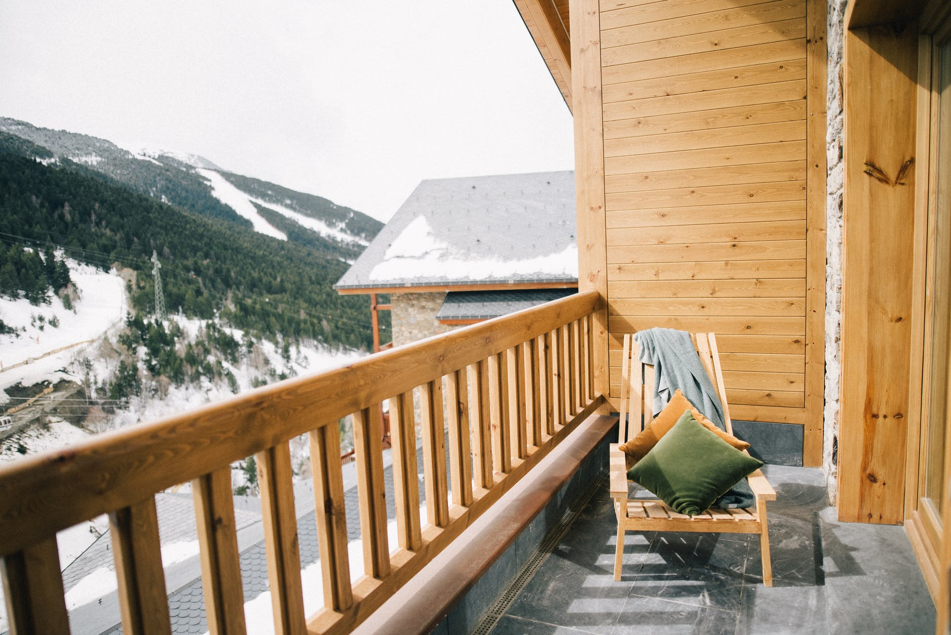 brown wooden chair on a veranda with view of a snowy mountain