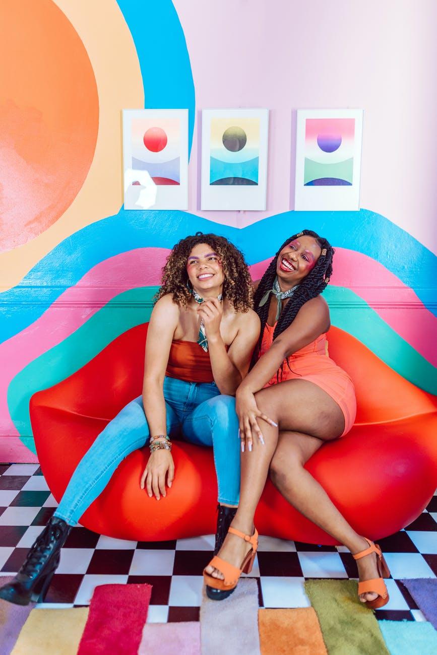two women sitting on lips shape sofa