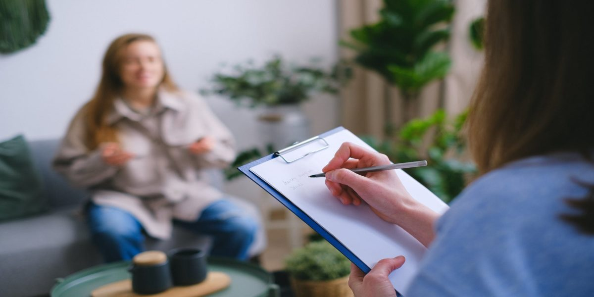 crop psychologist taking notes during appointment