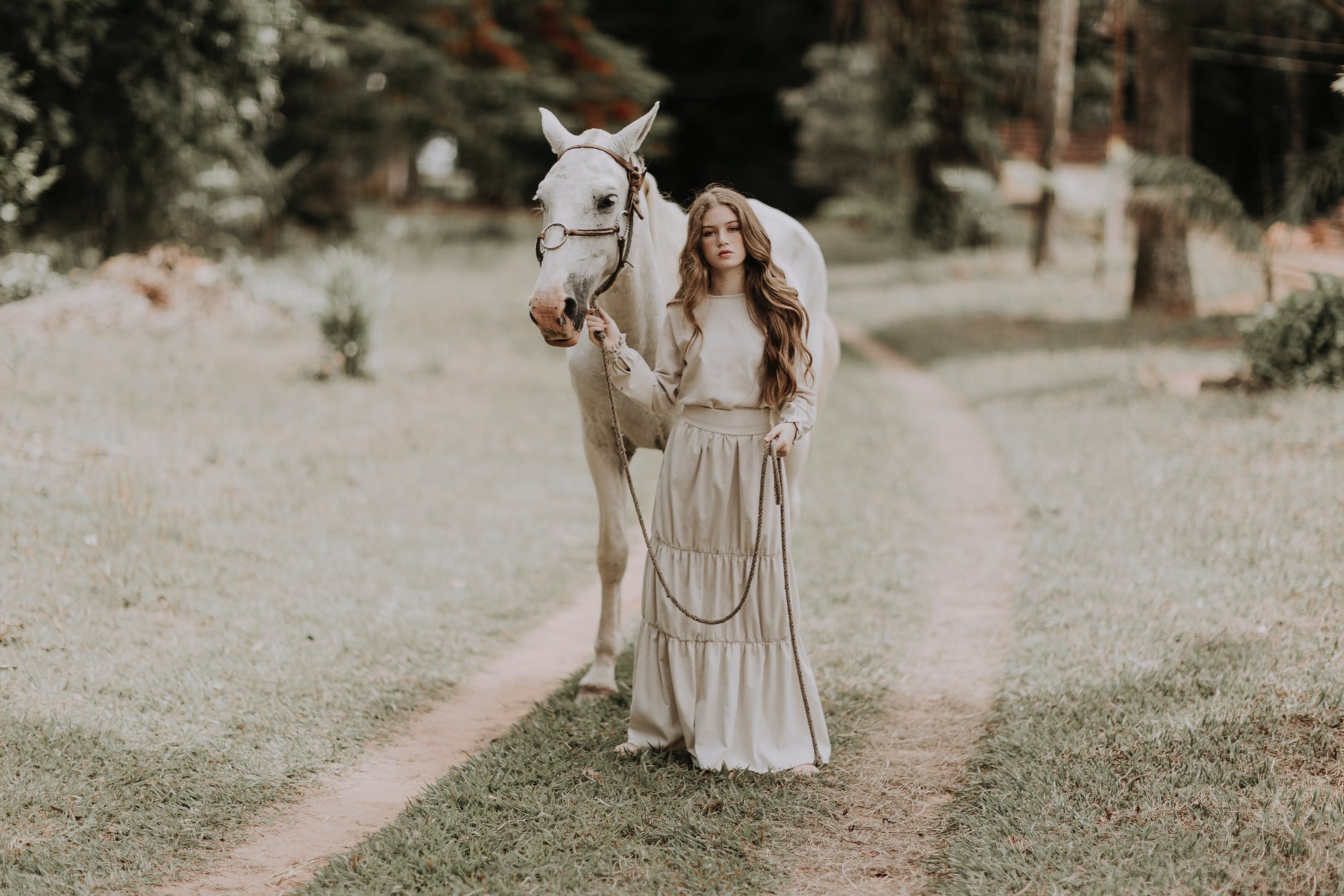 elegant young teenage female standing in green park with horse