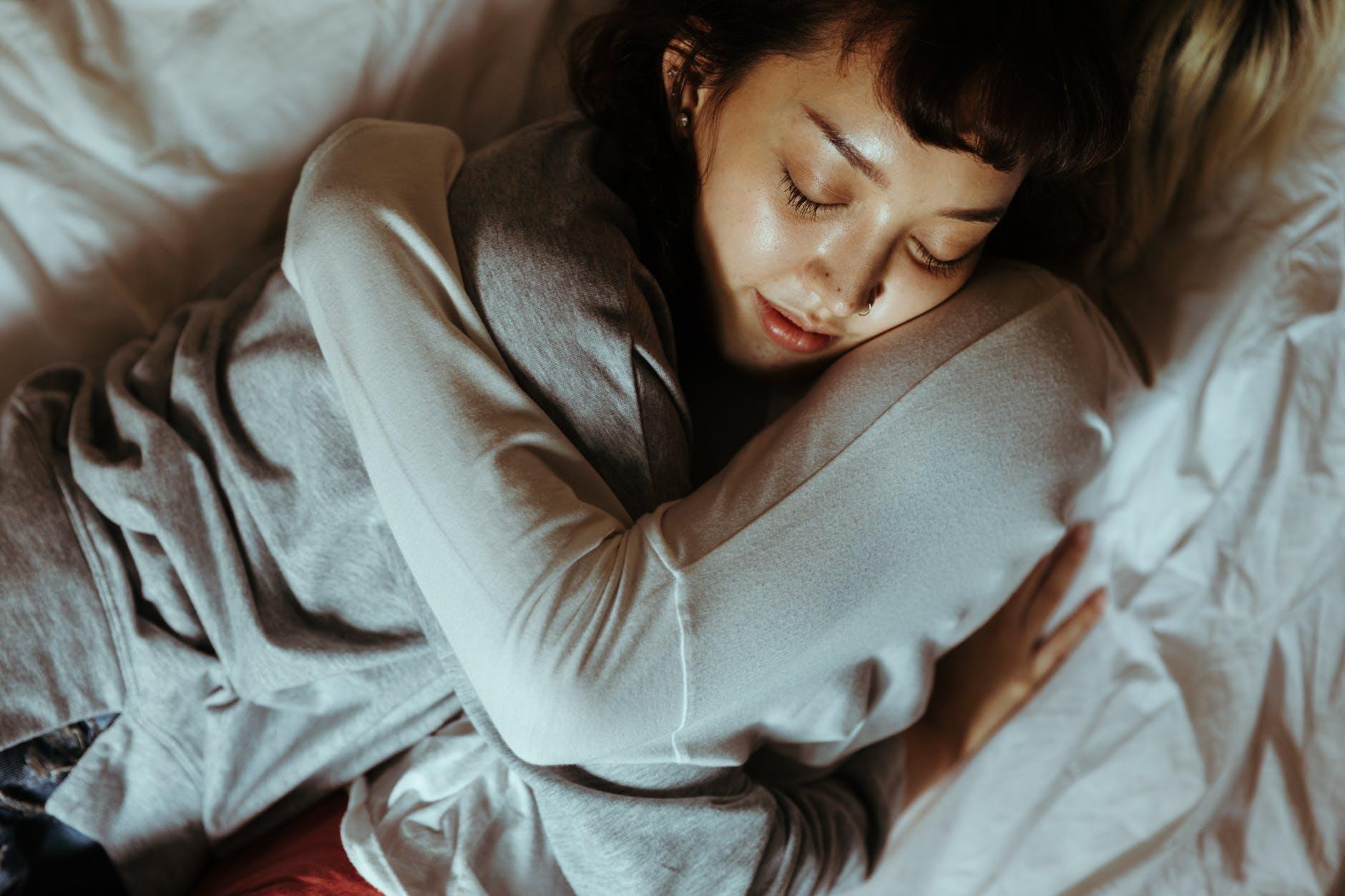 women hugging in bed