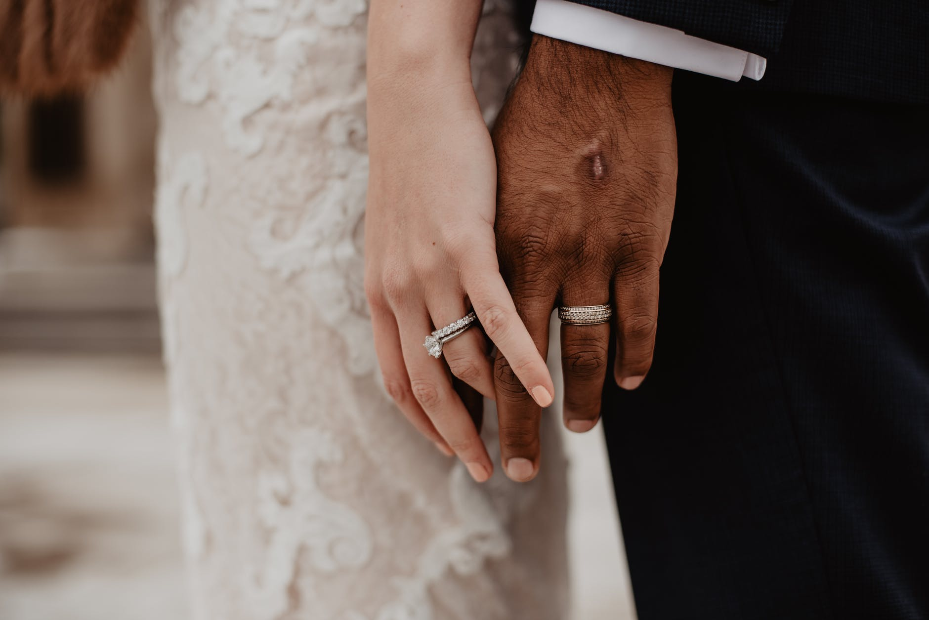 two persons wearing silver colored rings