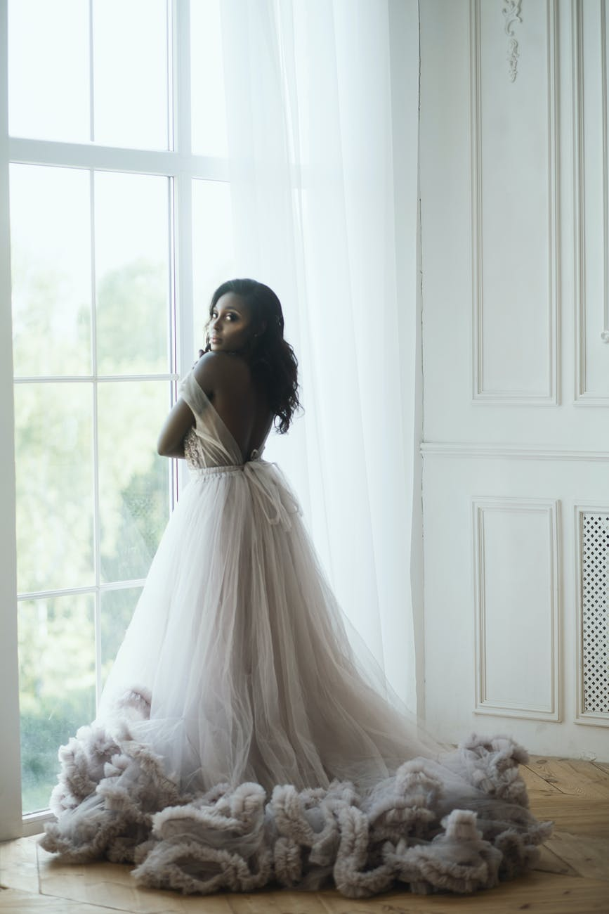 woman in white wedding dress standing near the window