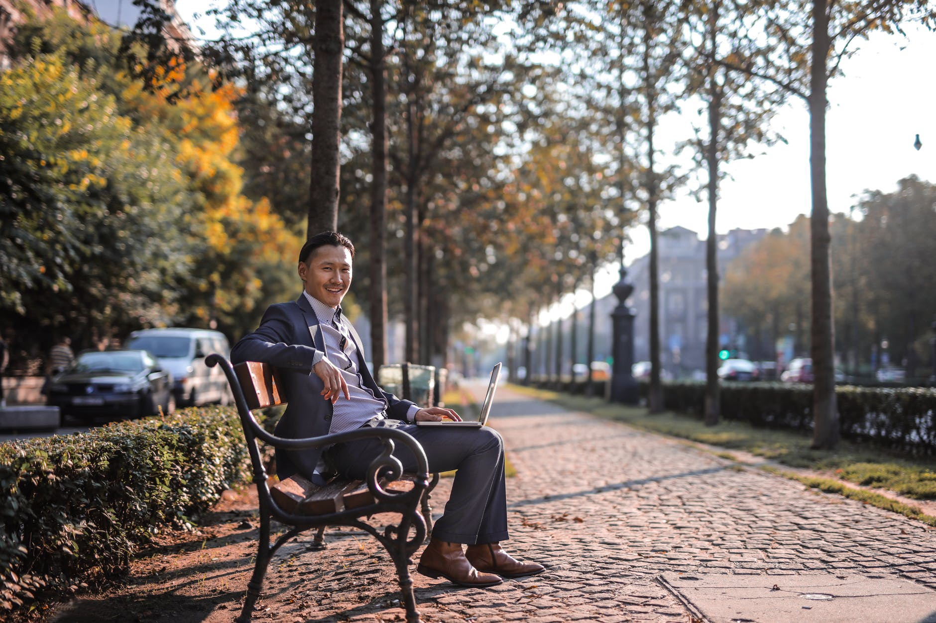 man in grey suit sitting on park bench using laptop