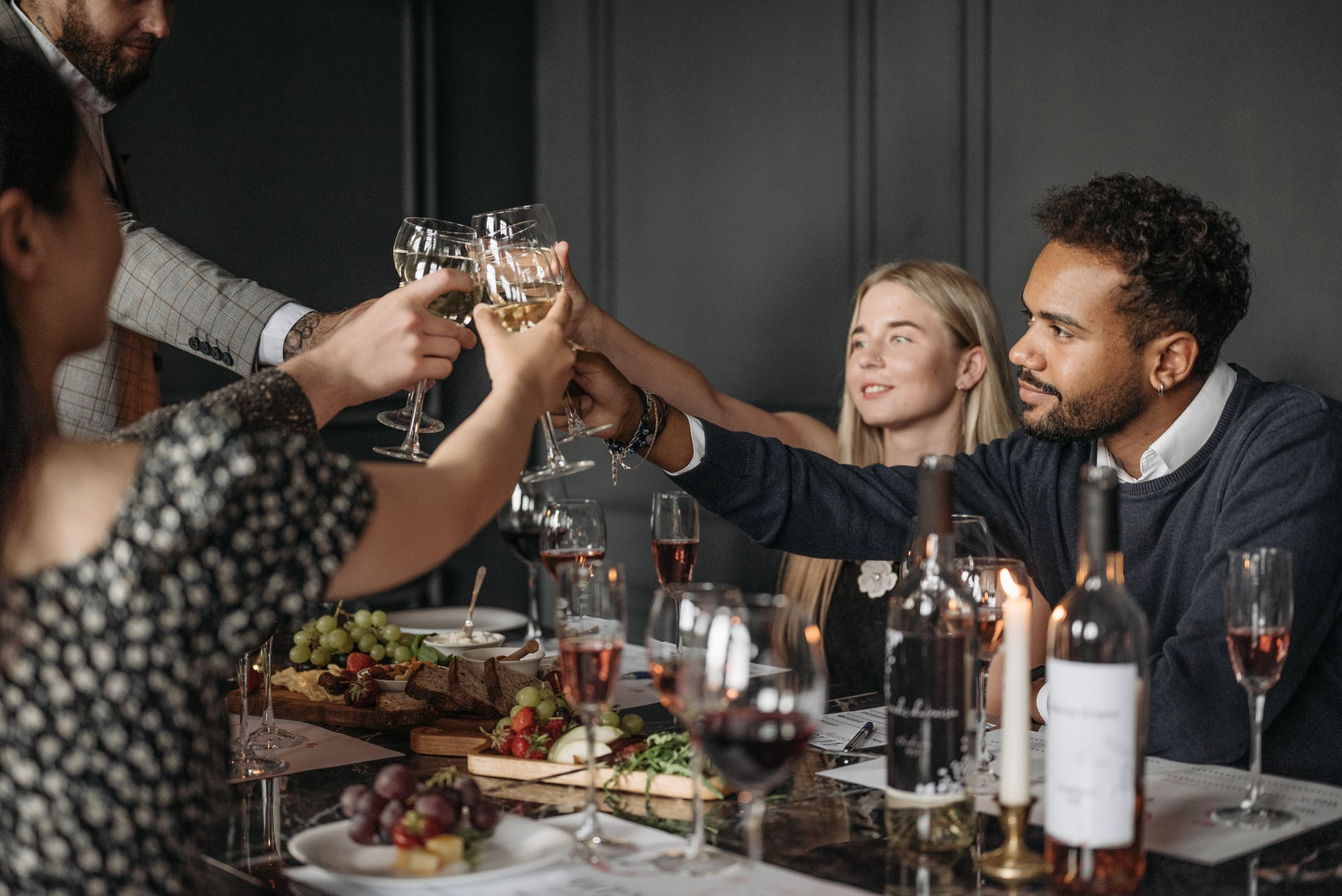 people holding a glass of wine at the table